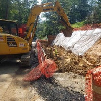 Contractor excavating Retaining Wall #3 bottom footing over cais-son, as preparation before forming and placing re-bars.
