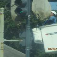 Removing the burlap covers on the new traffic signals to get ready for signals to be activated by DDOT.