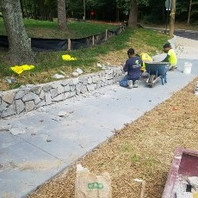 Contractor preparing wall surface to receive stone facing work and top coping finish.