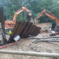 Contractor at Phase 3 Bridge area flood aftermath destruction, cleaning debris and restoring sheet piles.