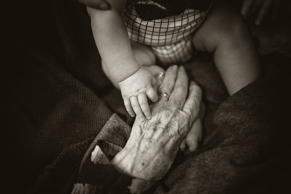 Elderly Person and Baby Holding Hands