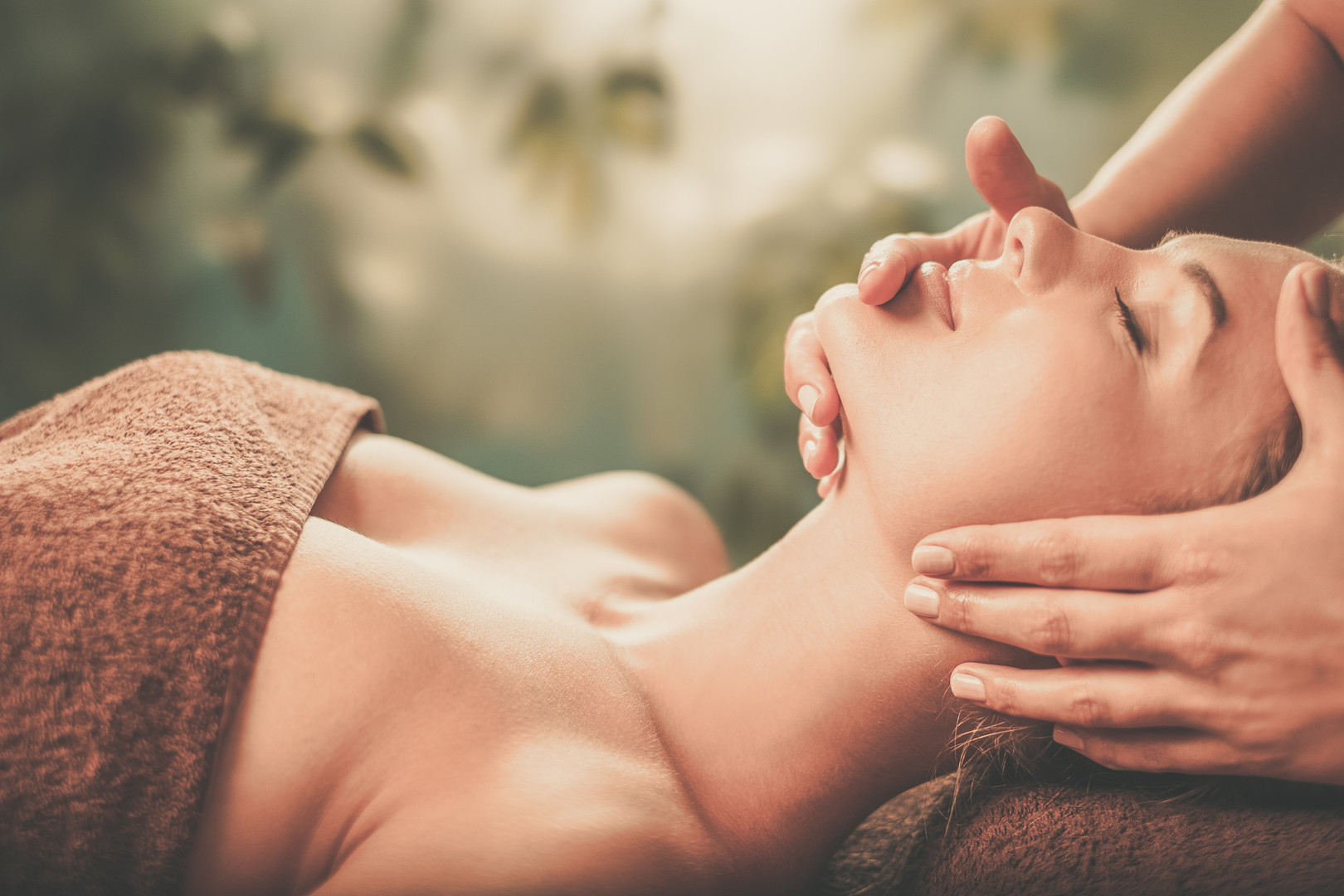 Young woman having face massage in a spa
