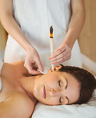 Young woman getting an ear candling trea