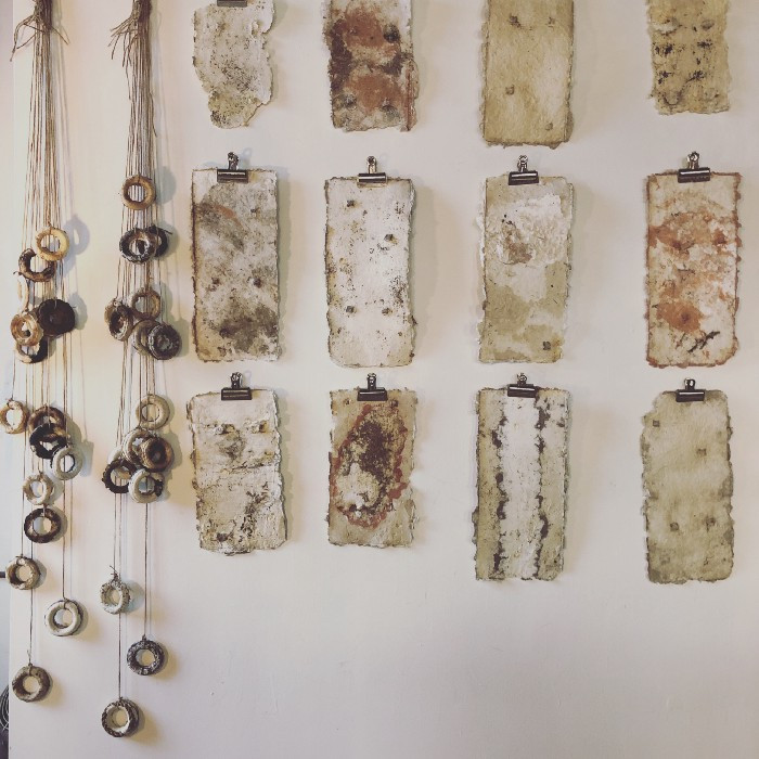 An array of handmade paper stained with railroad rust on one of Mitchell's studio walls