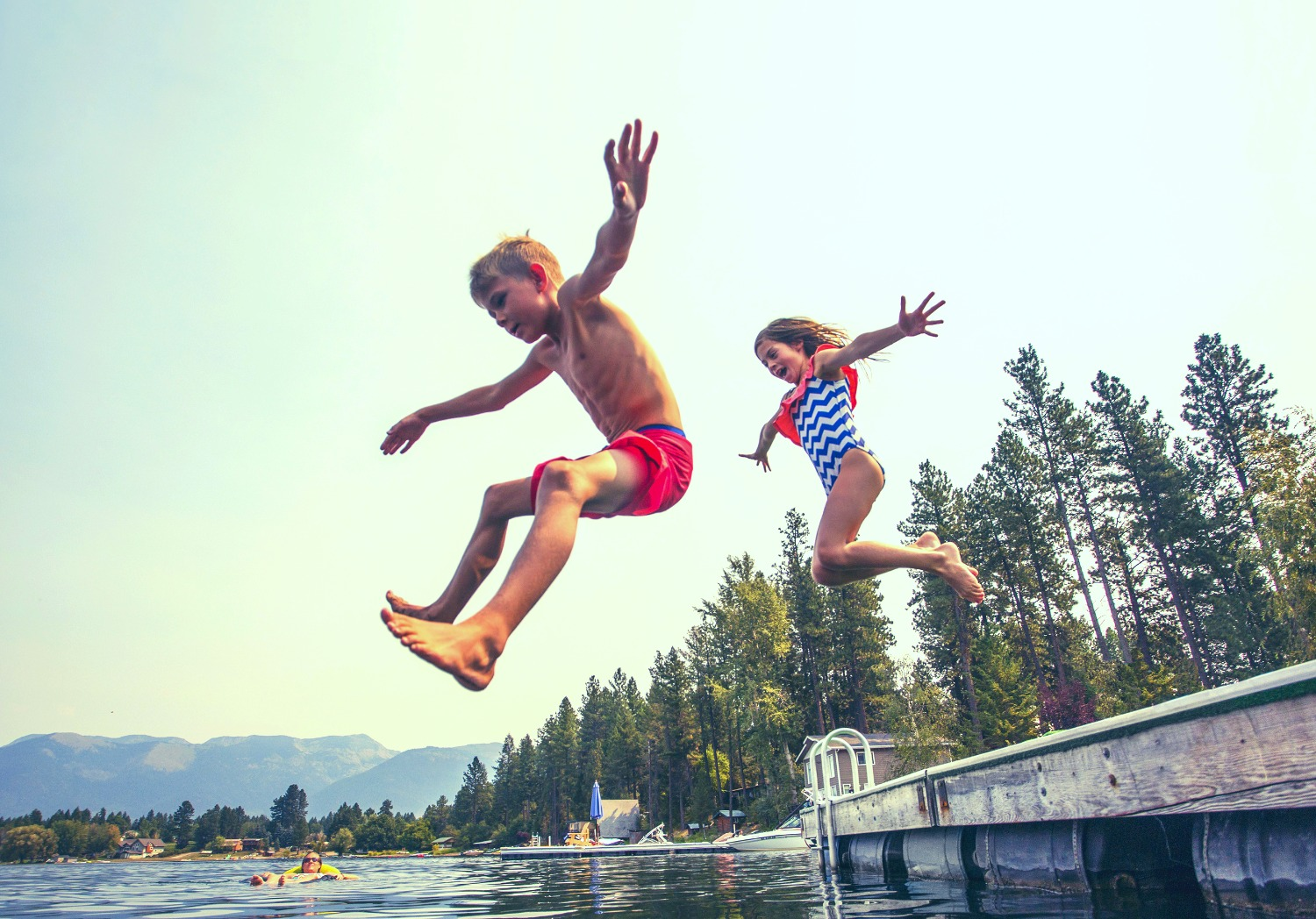 Kids jumping off the dock into a beautiful mountain lake. Having fun on a summer vacation at the lak