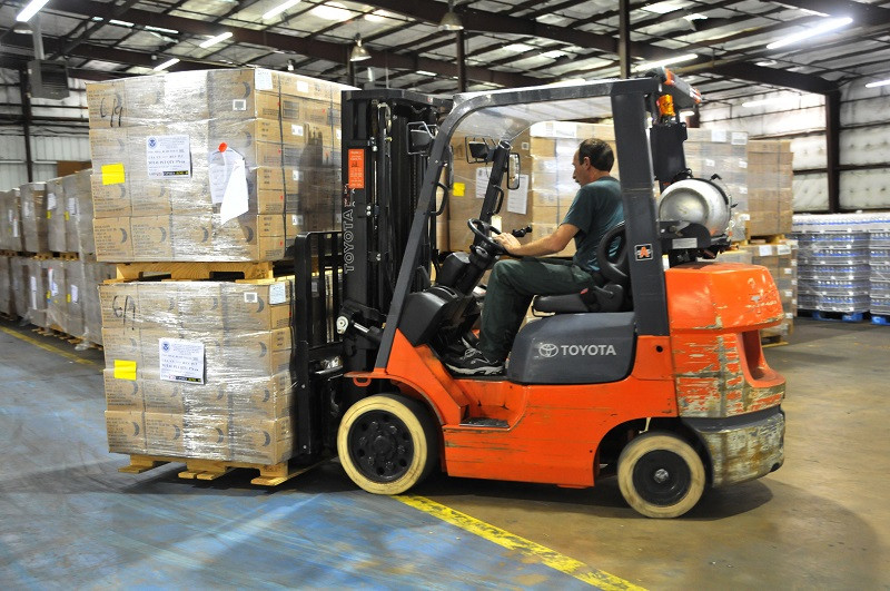 Man on a forklift in a warehouse working