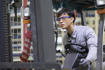 chinese asian man driving forklift with yellow googles