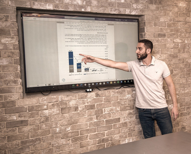 דביר בשן מצביע על גרף במהלך הצגה של תכנית עסקית של סטארטאפ