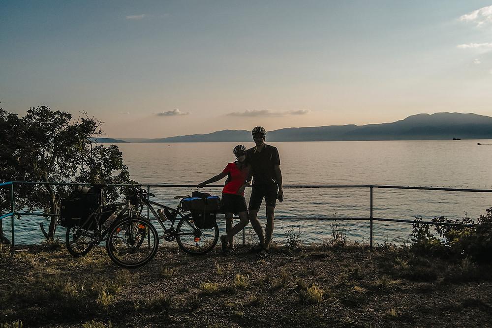 fotka dvojice bicyklistov v pozadí s chorvátskym morom a západom slnka