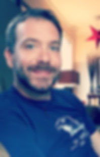 Photo of Bryan Borland smiling in a living room, wearing a t-shirt with an eagle. A red star hangs from the ceiling in the background.