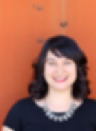 Photo of Janine Joseph smiling against an orange backdrop, wearing a black short-sleeved top and an ornate necklace.