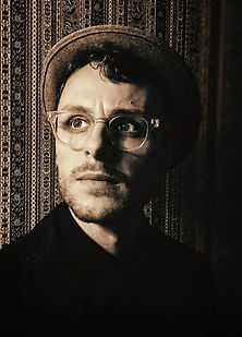Sepia-toned photo of Seth Pennington wearing a hat, glasses, and a dark shirt, against a backdrop of ornate wallpaper.