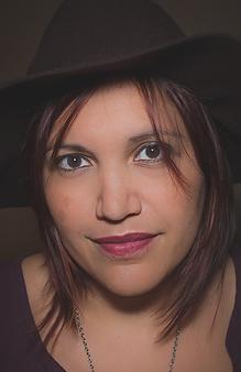 Photograph of Kai Coggin wearing a floppy black hat.