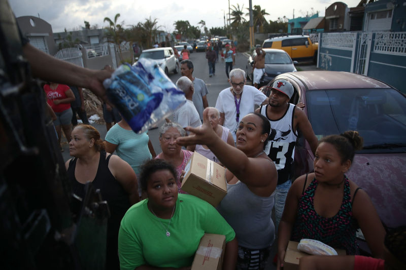 Hurricane Maria survivors receive food and water being given out by volunteers and municipal police as they deal with the aftermath of Hurricane Maria on Sept. 28, 2017, in Toa Baja, Puerto Rico. (Joe Raedle/Getty Images)
