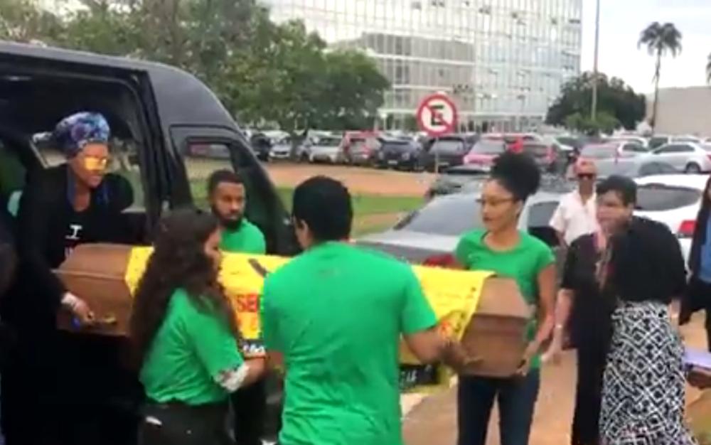 Representantes da Anisitia Internacional carregam caixão em frente ao Ministério da Justiça para pedir redução dos homicídios da população negra no Brasil (Foto: Facebook/Reprodução)