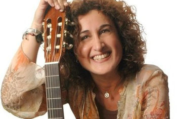 May Nasr smiling with hand on top of guitar