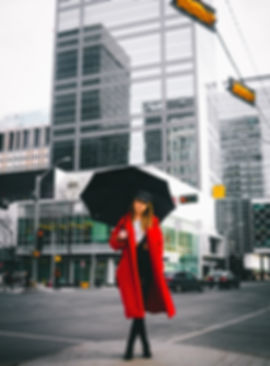 Female subject in a red coat holding an umbrella with downtown Edmonton in he background.