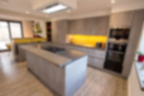 Modern grey kitchen in Oxfordshirewith central island unit and funky yellow splash back