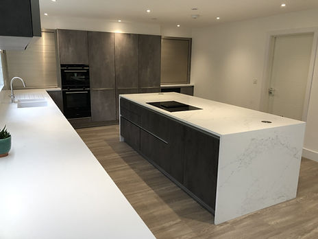 Island unit creates a very modern feel, lots of space wit white matt counter and tap area.