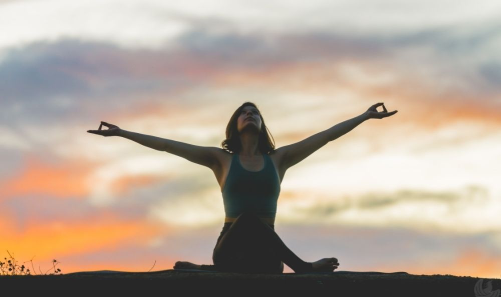 Woman with her hands extended to the sky.