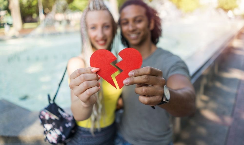 a happy young couple each holding half a heart shape which they are putting back together.