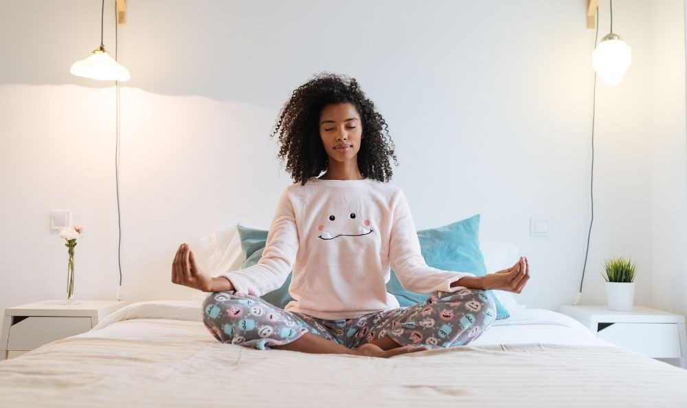 A woman meditating on a bed.