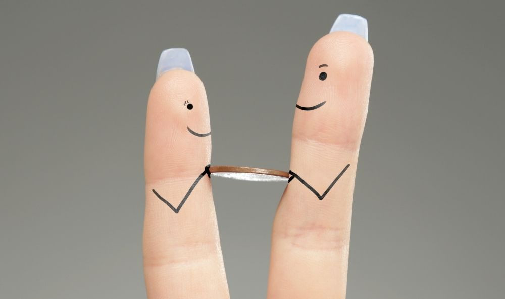 two fingers with faces drawn on holding a coin