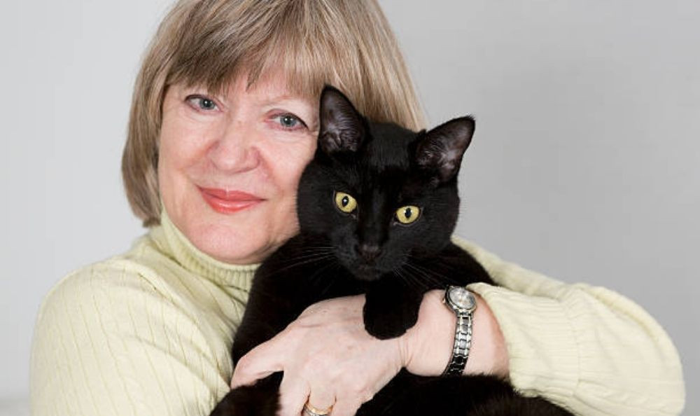 A woman (Brigid) holding a cat (Wednesday Adams)