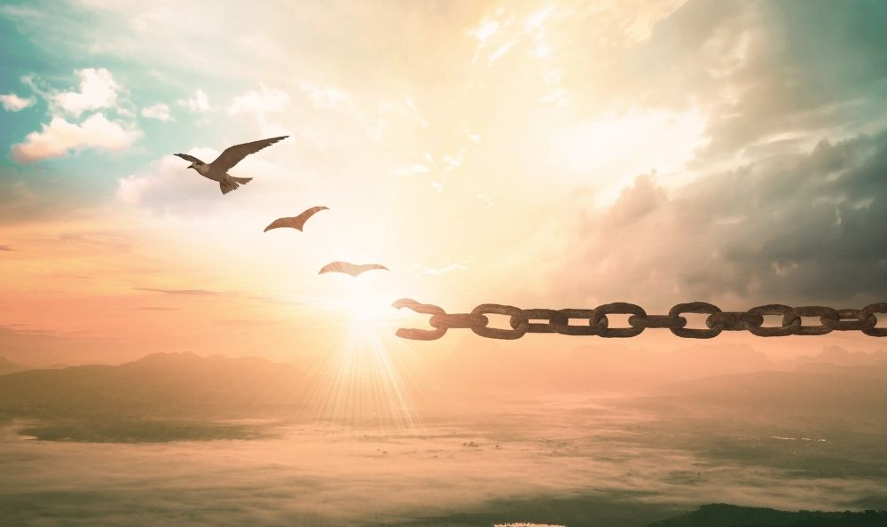 A chain breaking and doves flying from the break.