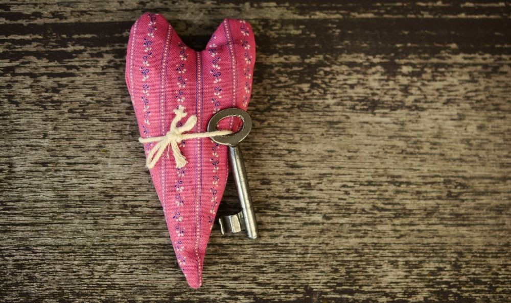 A heart cushion with a key tied to it.
