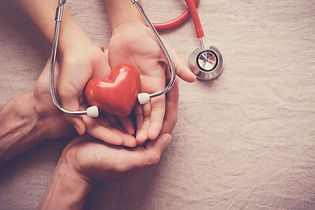 manos-sosteniendo-corazon-rojo-estetosco