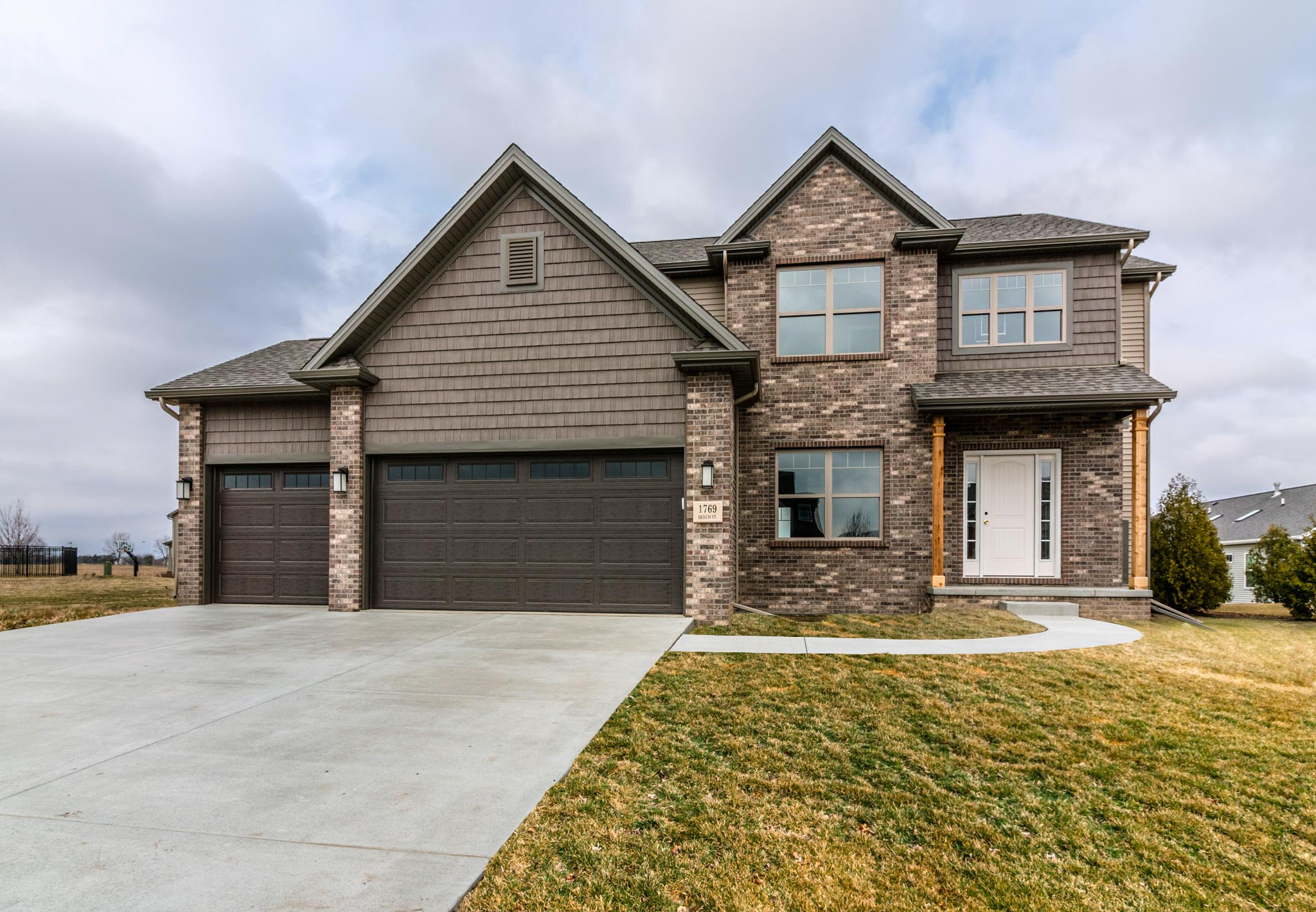 two story home with brown garage doors, brown brick, brown and tan siding in Normal il