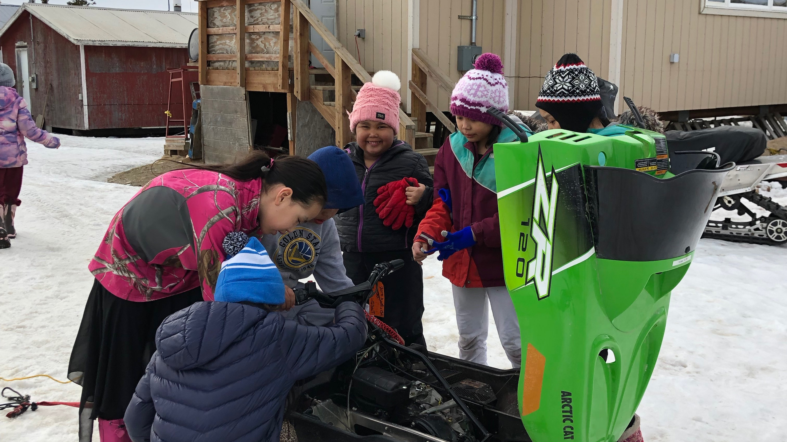 The kids working on their snowmobile
