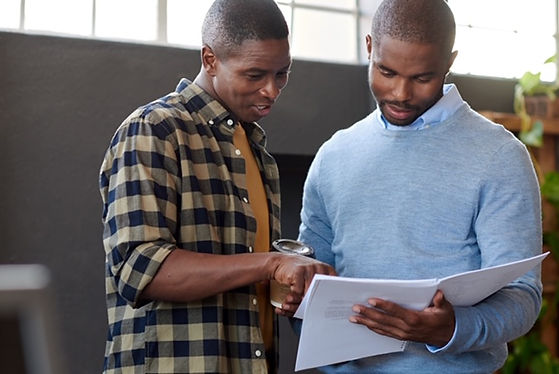 Two black men looking at paperwork - wit