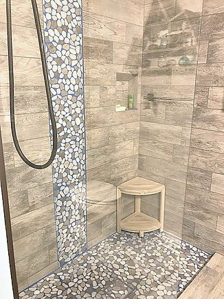 Image of shower with wood like tile and river rock accents