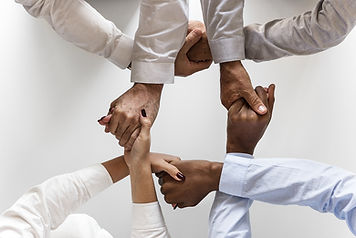 Image of 4 people grasping each other's hands to form a circle