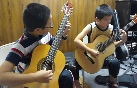 Image of Douglas Seth students practice guitar
