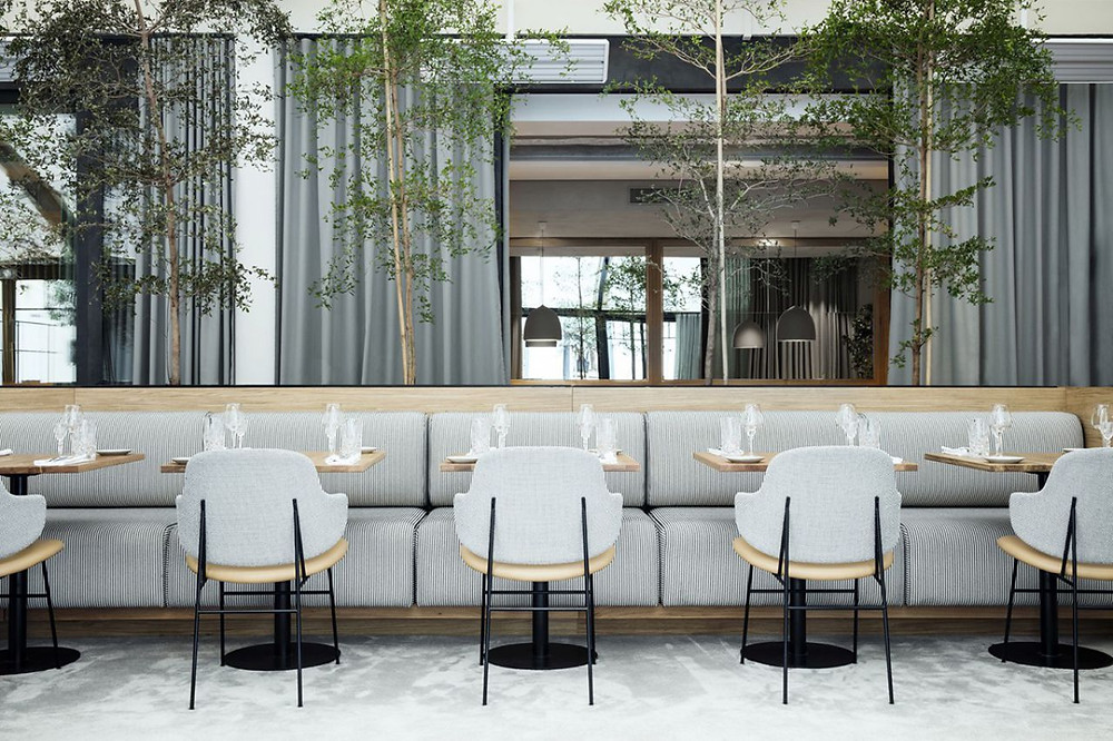 Flora Danica's sofas and chairs are upholstered with Remix, Colline is used on bar stools, and curtains are crafted from Time. The ambience is shaped, in part, by green textiles, botanical drawings and natural stone used for the bar. The palette for the brasserie is supplemented by grey notes, which can be seen on the herringbone floor, curtains and chairs.  Copenhague has a more formal, intense atmosphere. Harald is utilised for chairs, Sonar for the curved bench and the curtains are made from Time. The dark blue hues of the leather chairs and textiles create a sophisticated contrast with the white ceilings and porcelain.  Designed by Danish design studio GamFratesi, both spaces unite contemporary and classical mid-century Danish design features. The furniture, lighting, cutlery, textile and decorative items are produced by Danish manufactures or selected from vintage pieces.  La Maison du Danemark is located on the Champs-Élysées in Paris.