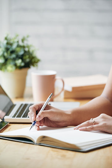 unrecognizable-woman-sitting-desk-indoor