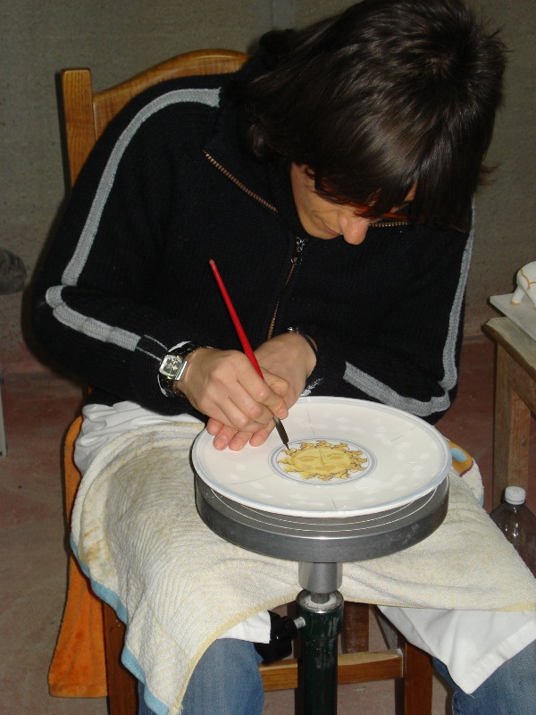 Painter hand paints a plate in Sicily