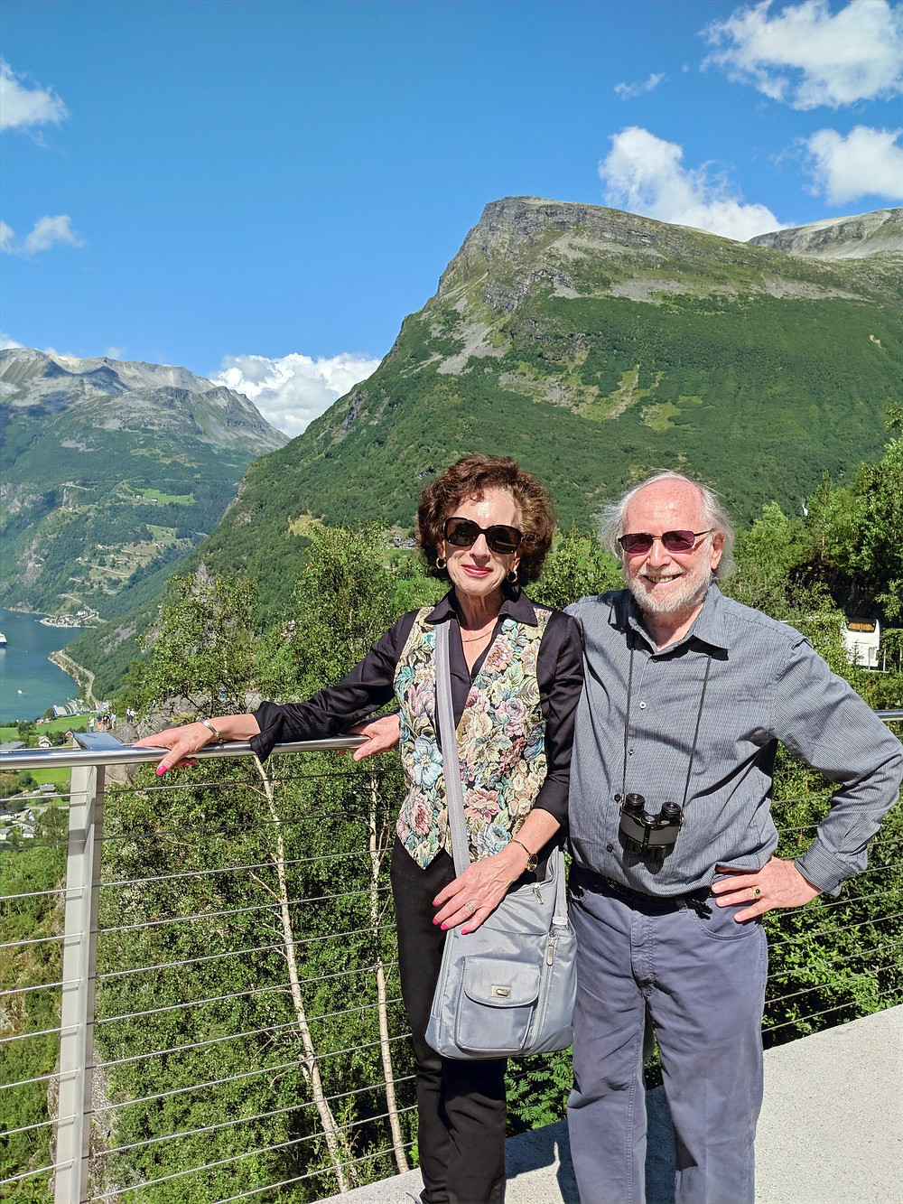 Donna and her husband pose in front of a mountain overlooking a river in Norway.