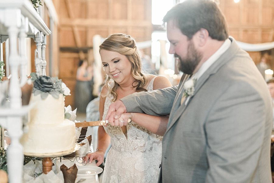 bride and groom cutting the cake at Red Oak Valley barn wedding reception