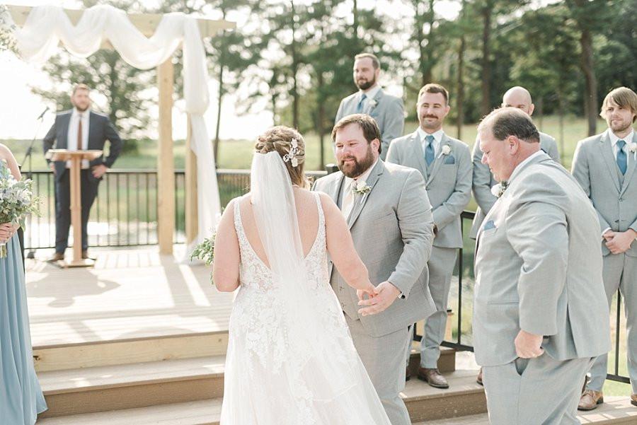 groom receives bride at outdoor lakeside ceremony at Red Oak Valley wedding venue