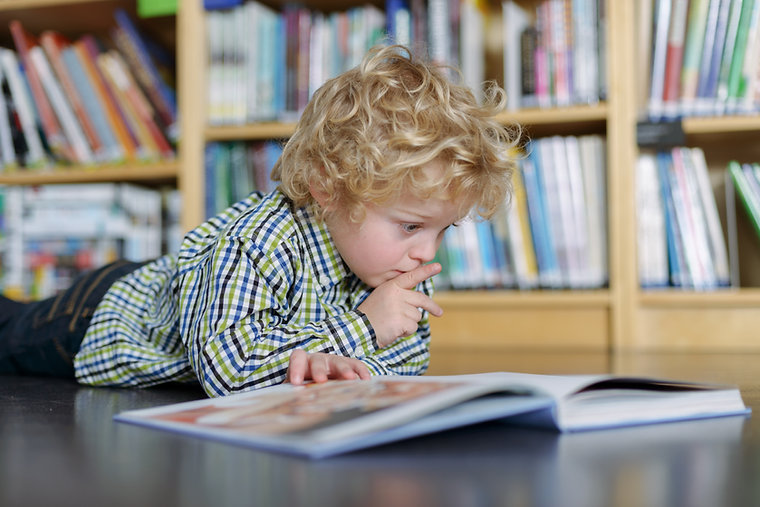 Young boy in front of book shelf
