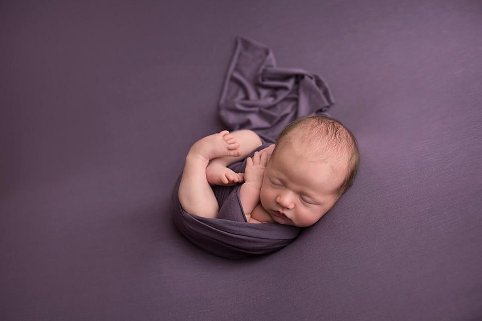 curly newborn on purple