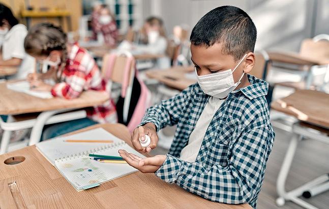 Schüler mit Mundmaske und am Hände desinfizieren