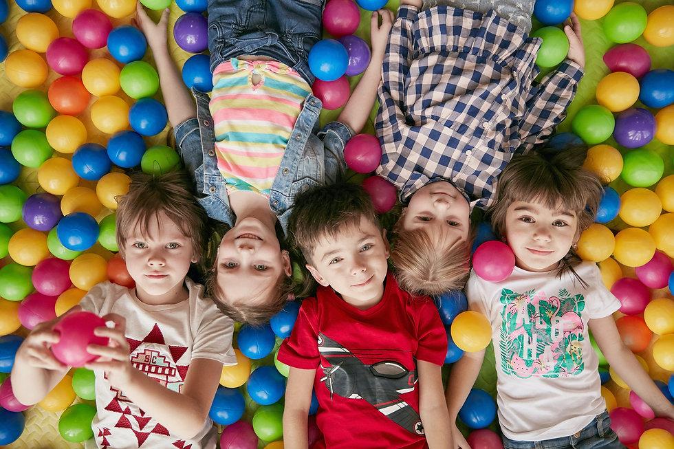 Kinder liegen auf kleinen, bunten Spielbällen
