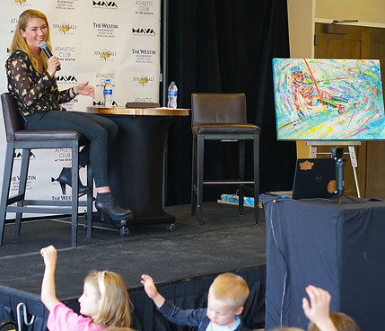 Mikaela Shiffrin answering questions at the Westin Riverfront in Avon, CO with my painitng of her in the background