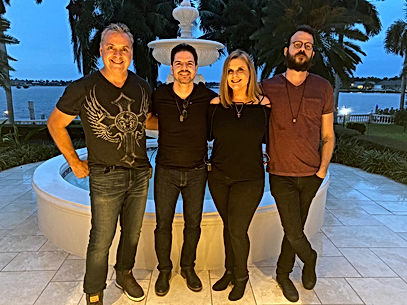 Exit Left Rock Band Blonde Woman and 3 Men in Front of Fountain with Ocean and Palm Trees in the Background