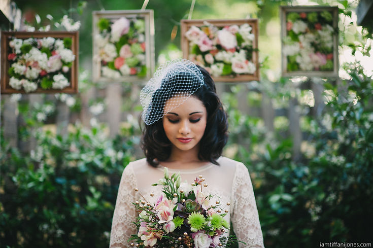 Bride holding bouquet with flower pergola background